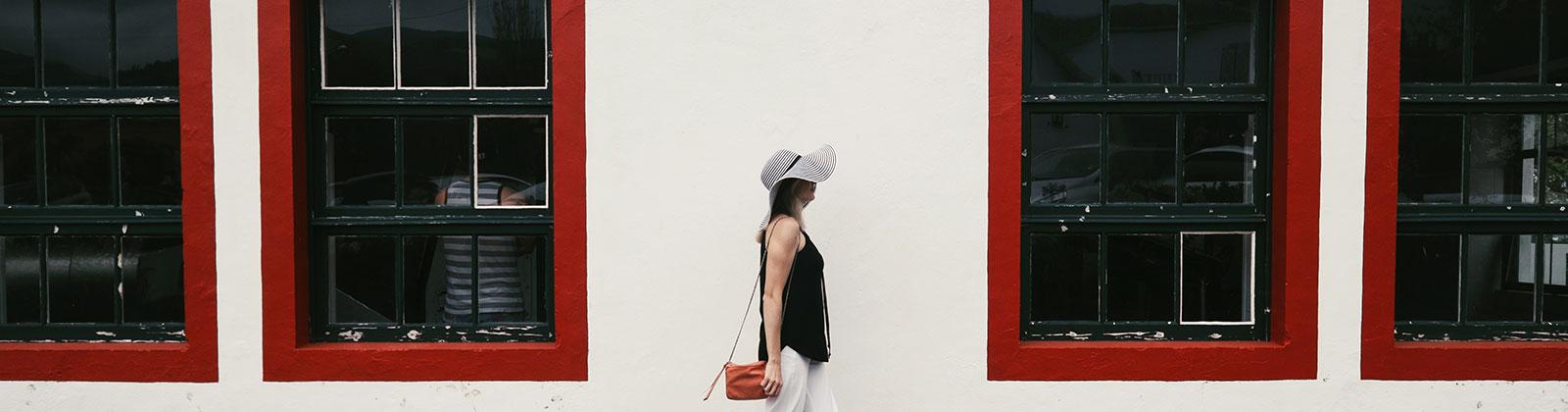 woman walking in front of windows