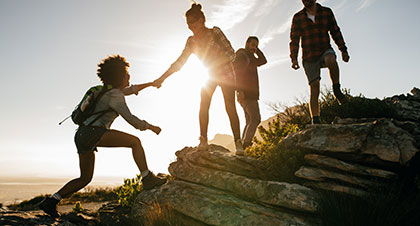 Group of people hiking with one woman giving a hand to another