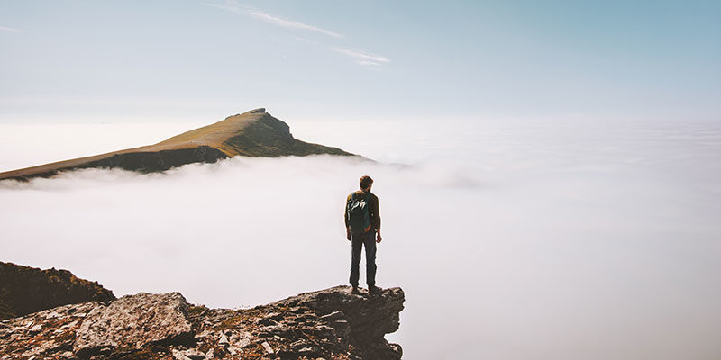 person standing on cliff with clouds below