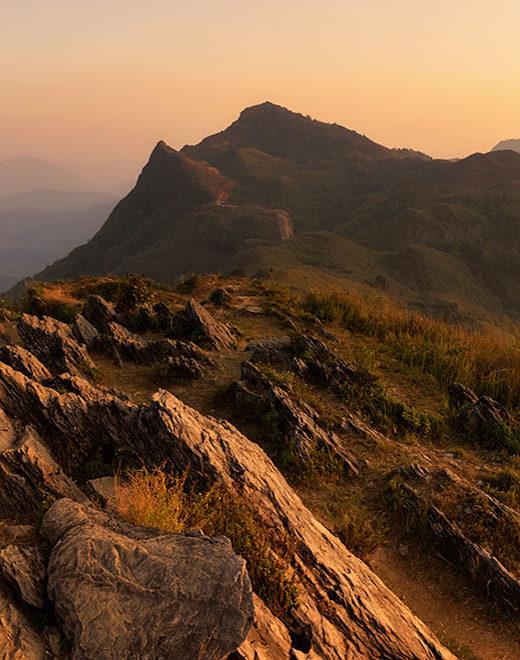 man on mountain looking at sunset