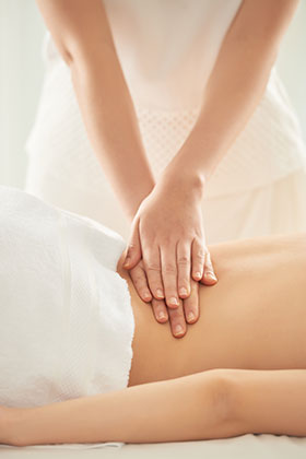 closeup of massage therapist hands on back of client
