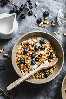 Homemade granola with greek yogurt and blueberries on a grey background, top view