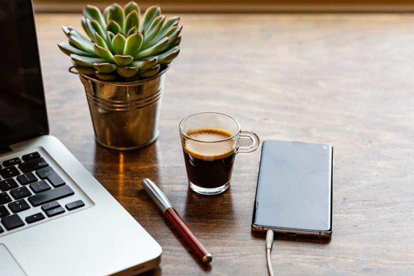 desk with laptop plant coffee cup and external hard drive